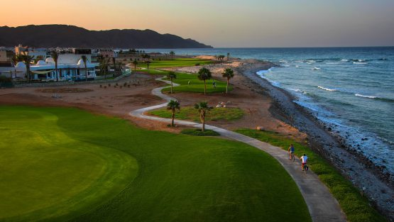 guests riding bicycle inside golf course at jebel sifah resort beside the ocean in oman