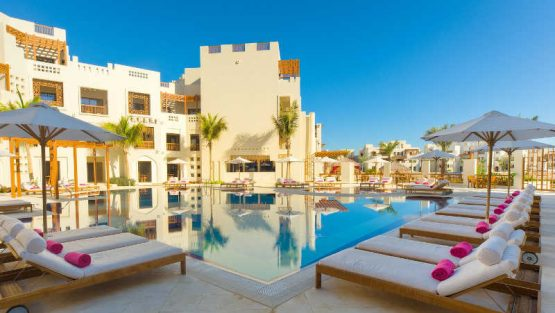 The pool view of Sifawy Boutique Hotel with sun lounges for day use in jebel sifah